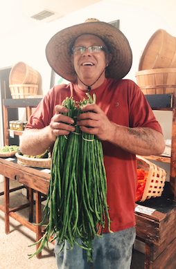 Jeff with his yard long beans in the farm store!