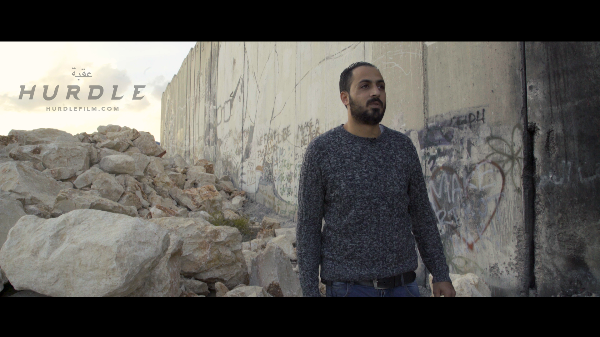 Documentary Subject Mohammad Speaking Near Separation Wall (CREDIT_ Hurdle).png