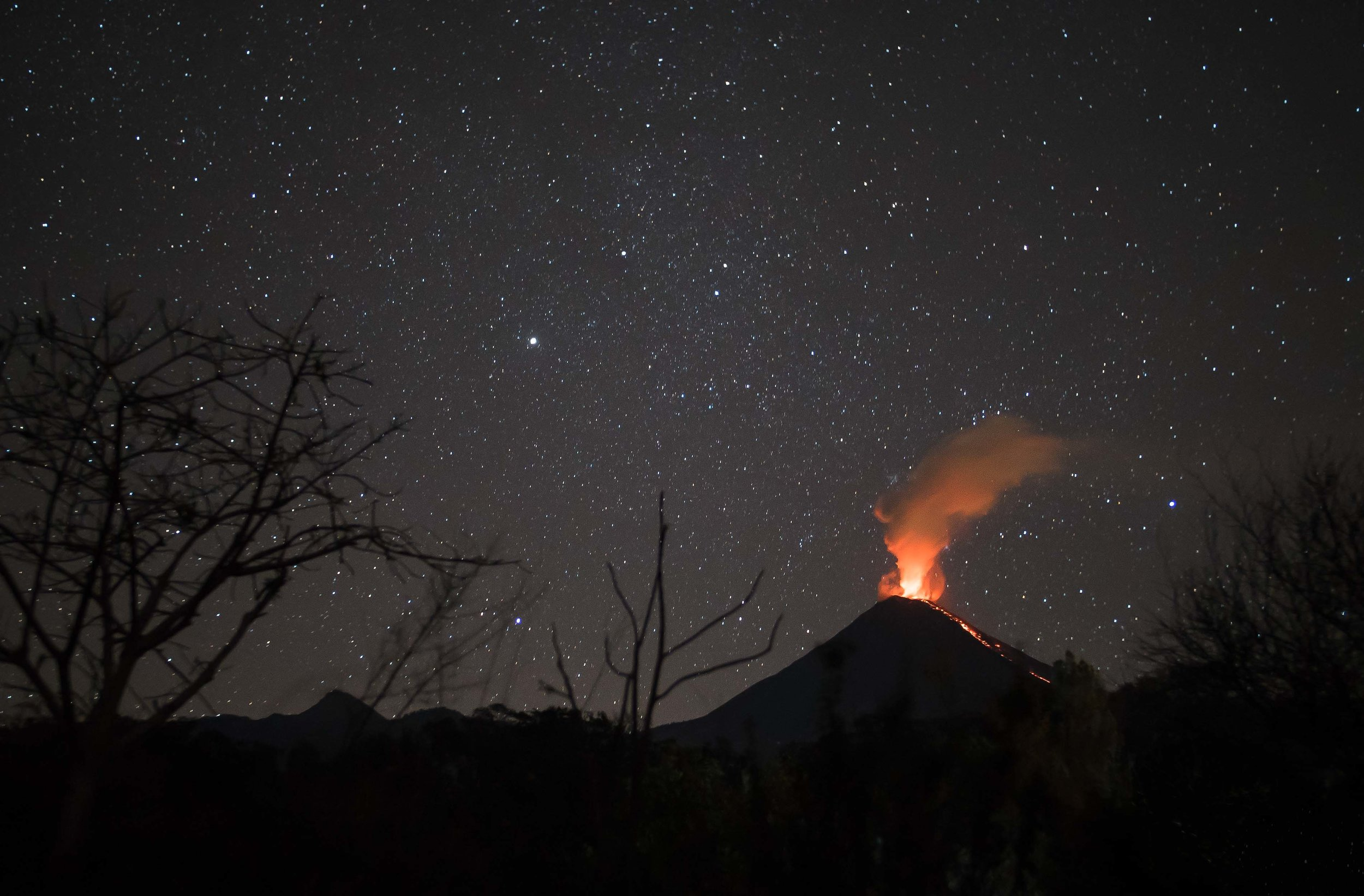 The Volcano of Colima erupting at night.