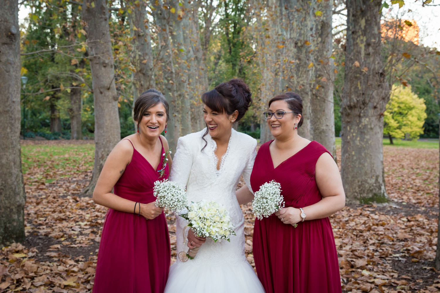 Four Daisies - wedding photography in Melbourne, Yarra Valley, Dandenong Ranges and Mornington Peninsula. Fitzroy Gardens, Melbourne city wedding photography. Bride and bridesmaids in red dresses.
