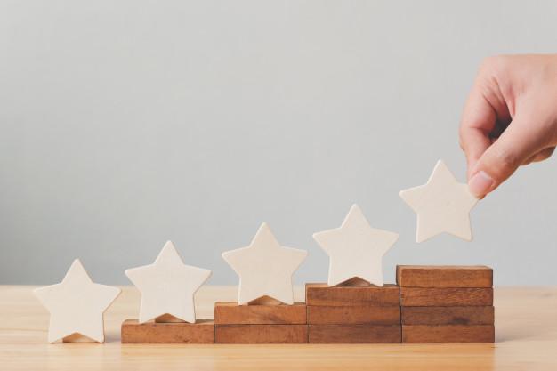hand-die-houten-vijfsterrenvorm-op-lijst-zet-de-beste-service-voor-het-beoordelen-van-klantervaringen_20693-160.jpg