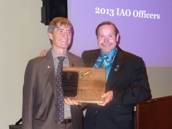 Recognizing the Past President, Dr. Rick Grant (right) presents Dr. Mike Lowry with the Gavel of Office, a plaque recognizing Dr. Grant's achievements as IAO President, 2012-2013.