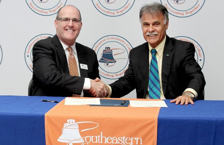 Tony Clarke, left, and Jose Sartarelli shake on a just-signed agreement between Southeastern Community College and UNC-Wilmington that will benefit students wanting to obtain a four-year degree.