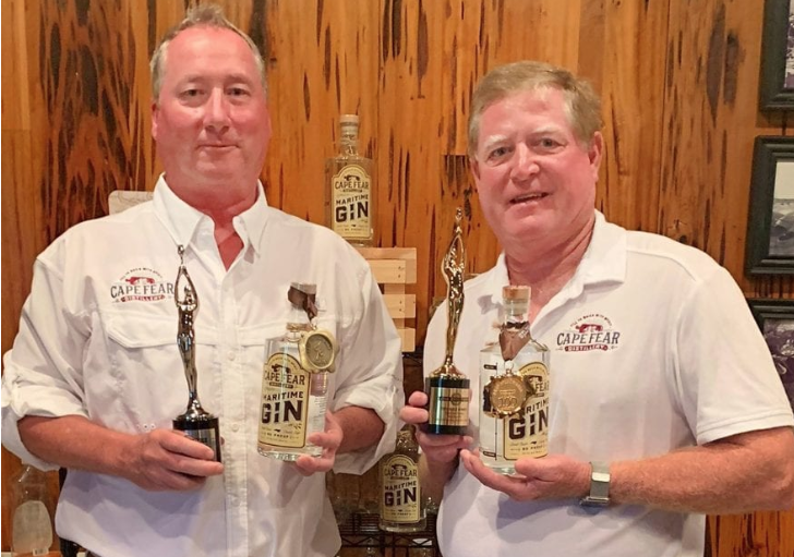 Cape Fear Distillery owner Alex Munroe and distiller Rick Neisler are pictured with awards for the company's Maritime Gin. Contributed photo