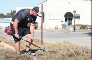 Todd Burney trims tall weeds and grass in front of the Columbus County Arts Council Saturday morning.