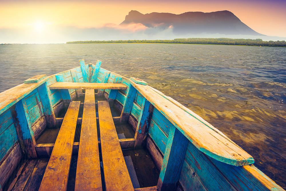 A wooden boat heading toward mountain
