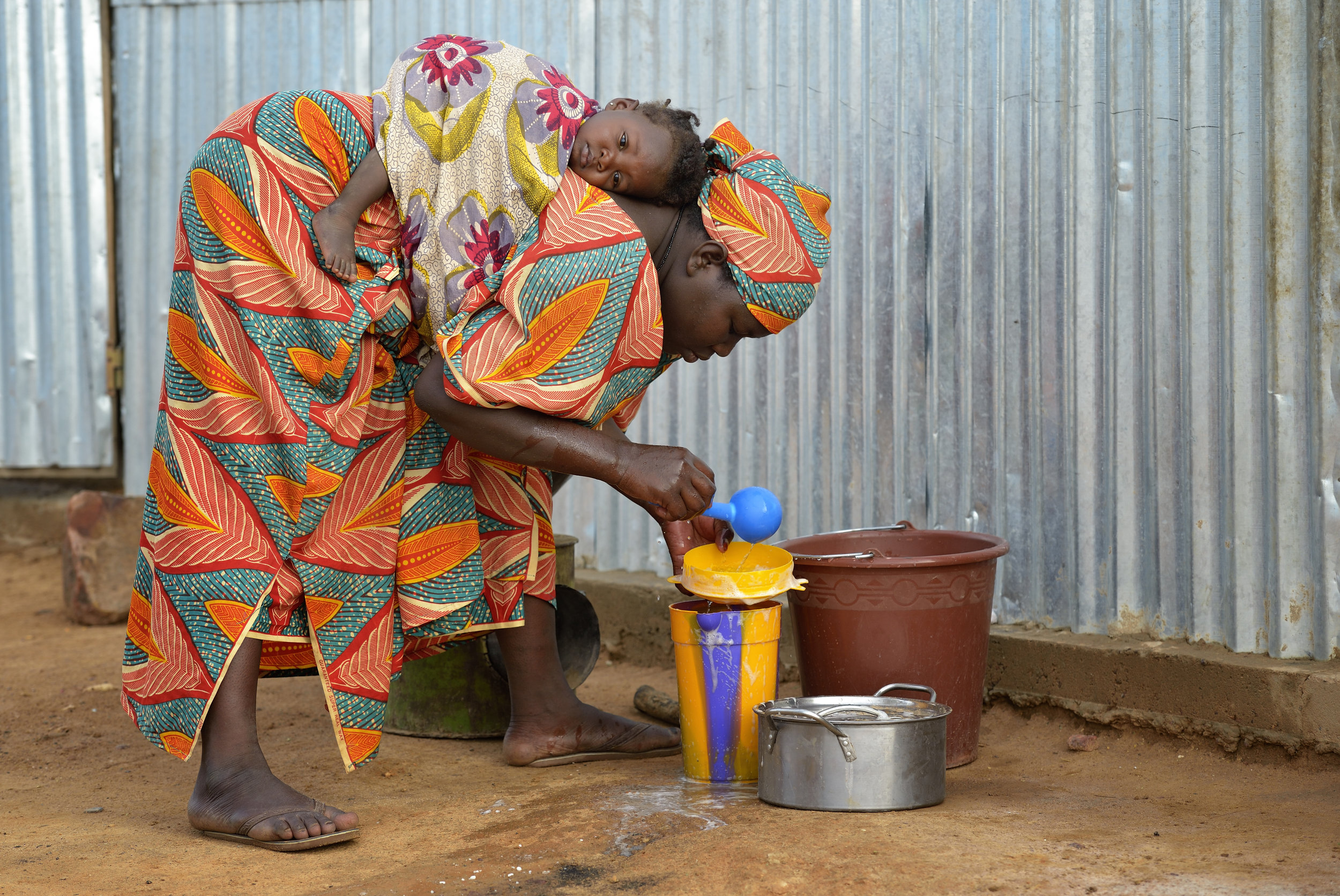 Umu Maiga starts a cooking stove as her one-month old daughter Hosemira rides along in a camp in Mopti, Mali