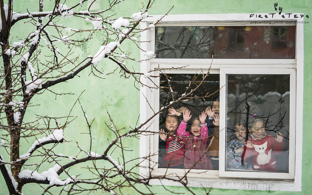 Children look through the window at the Yangji Daycare.