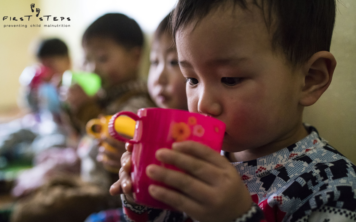 Careful sips of warm nutritious soymilk at the Yangji Daycare.