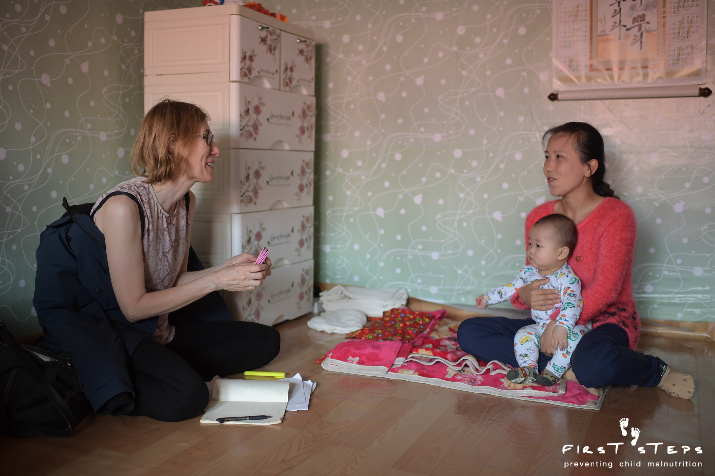 Susan Ritchie, First Steps' executive director, visits the home of Sprinkles recipient Mun Kum-Hae and her six-month-old son Kim Whi-Bok.