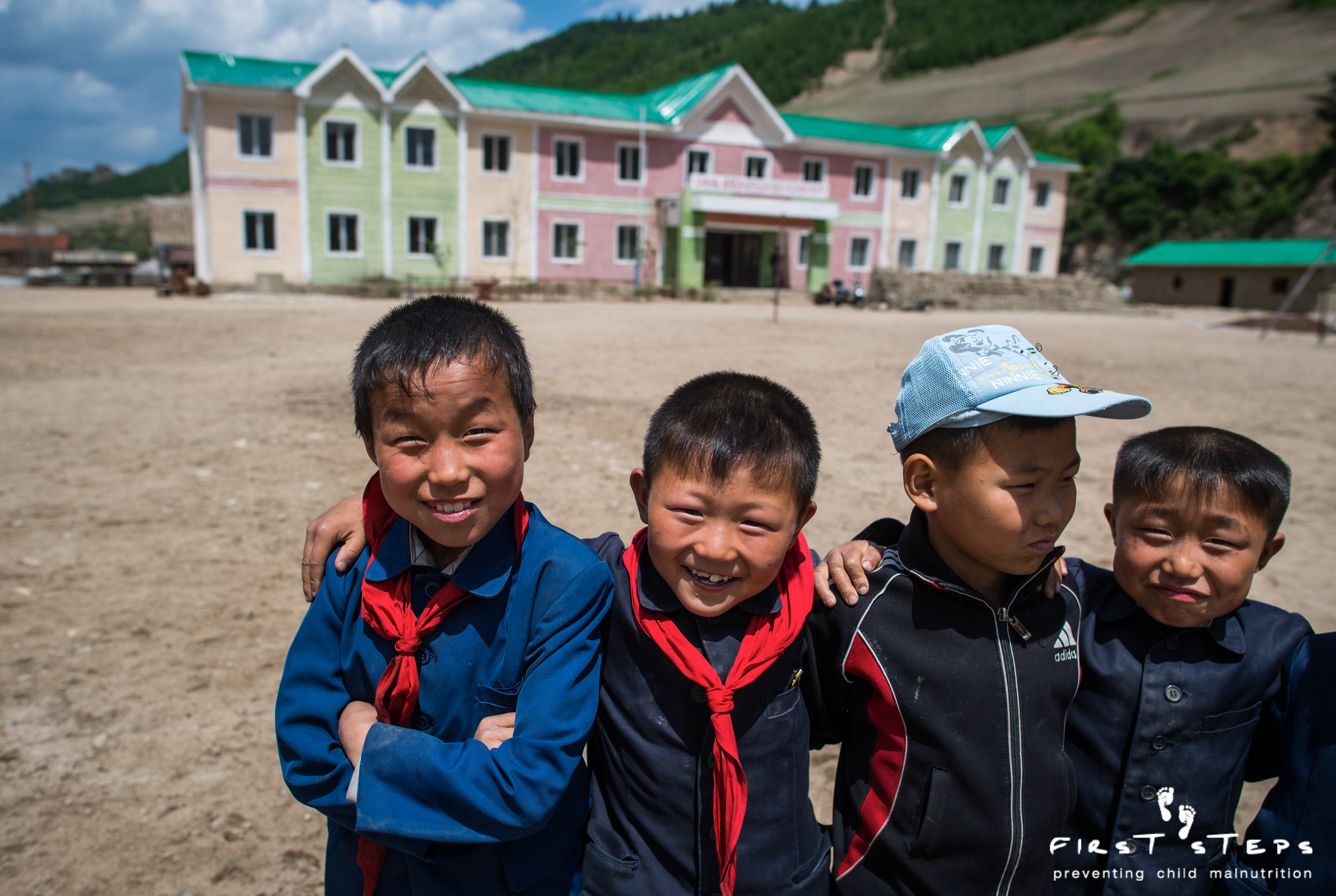 Children pose outside the Kwangyang School, rebuilt with roofing from First Steps.