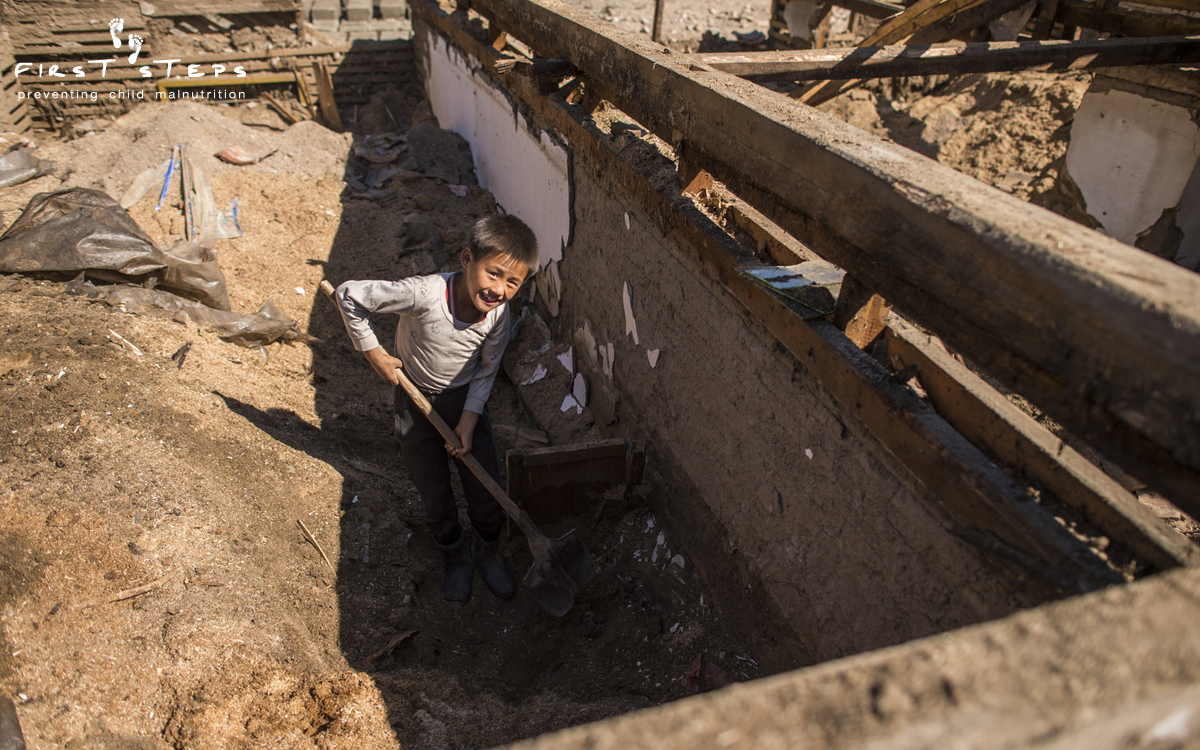 Kim Kum-Hyok(11) is digging through the ruins of his room looking for prized possessions. He and his family lost all their personal belongings in the flood.
