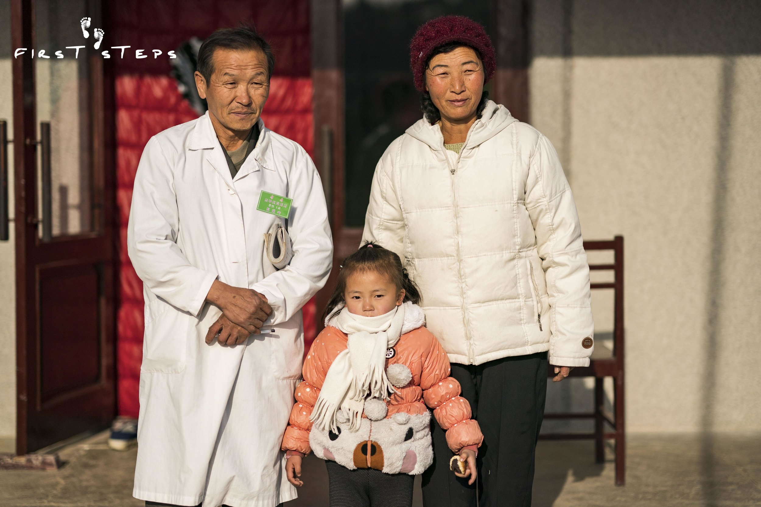 Dr. Kim Sun-Man, director of the Shinmi Policlinic, standing with his wife Mrs. Ri Yon-Ok and their four-year-old grand-daughter Na-Rye.