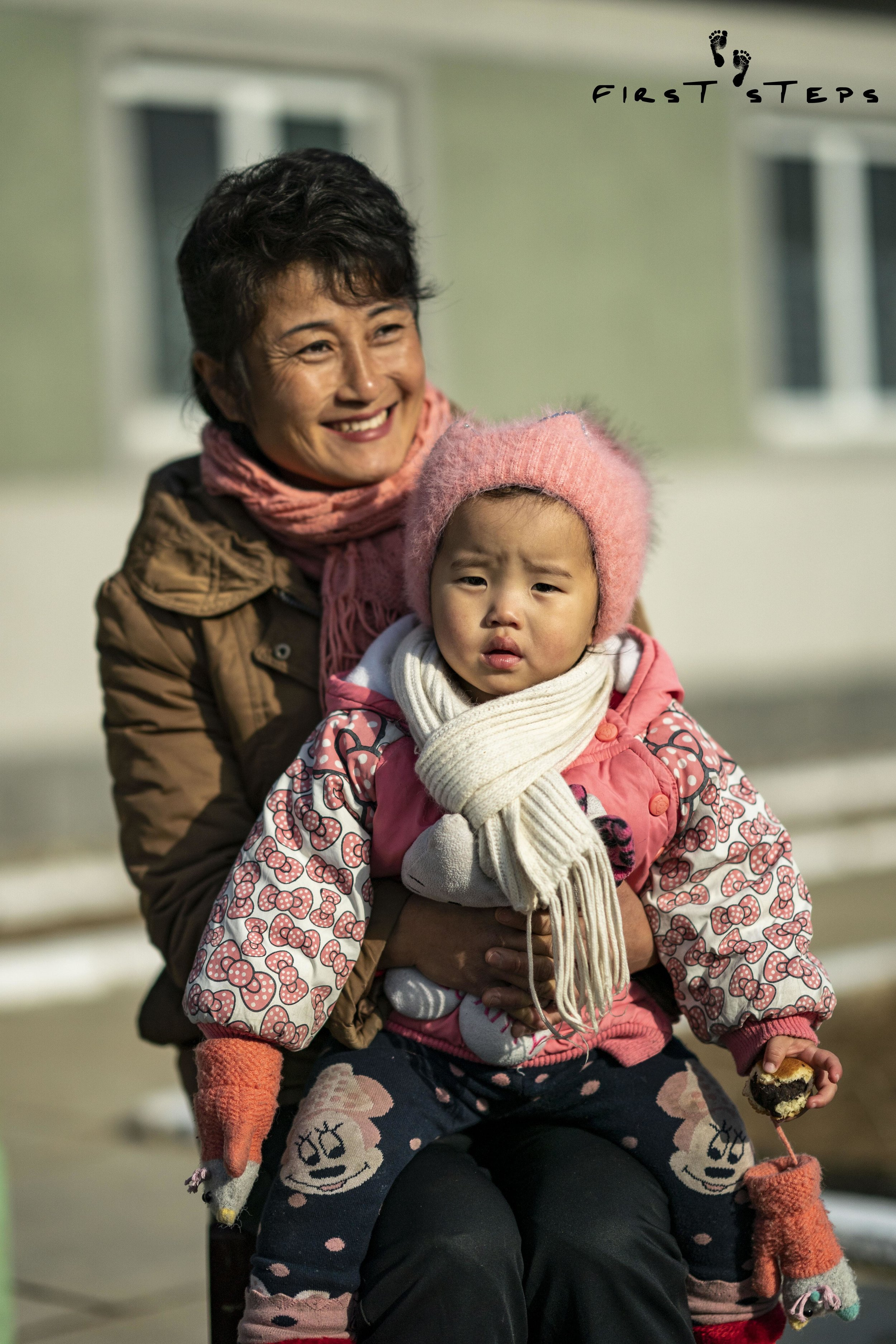 Mrs. O Mi-Yang and her one-year-old daughter Bok-Ryon outside the Shinmi Policlinic.