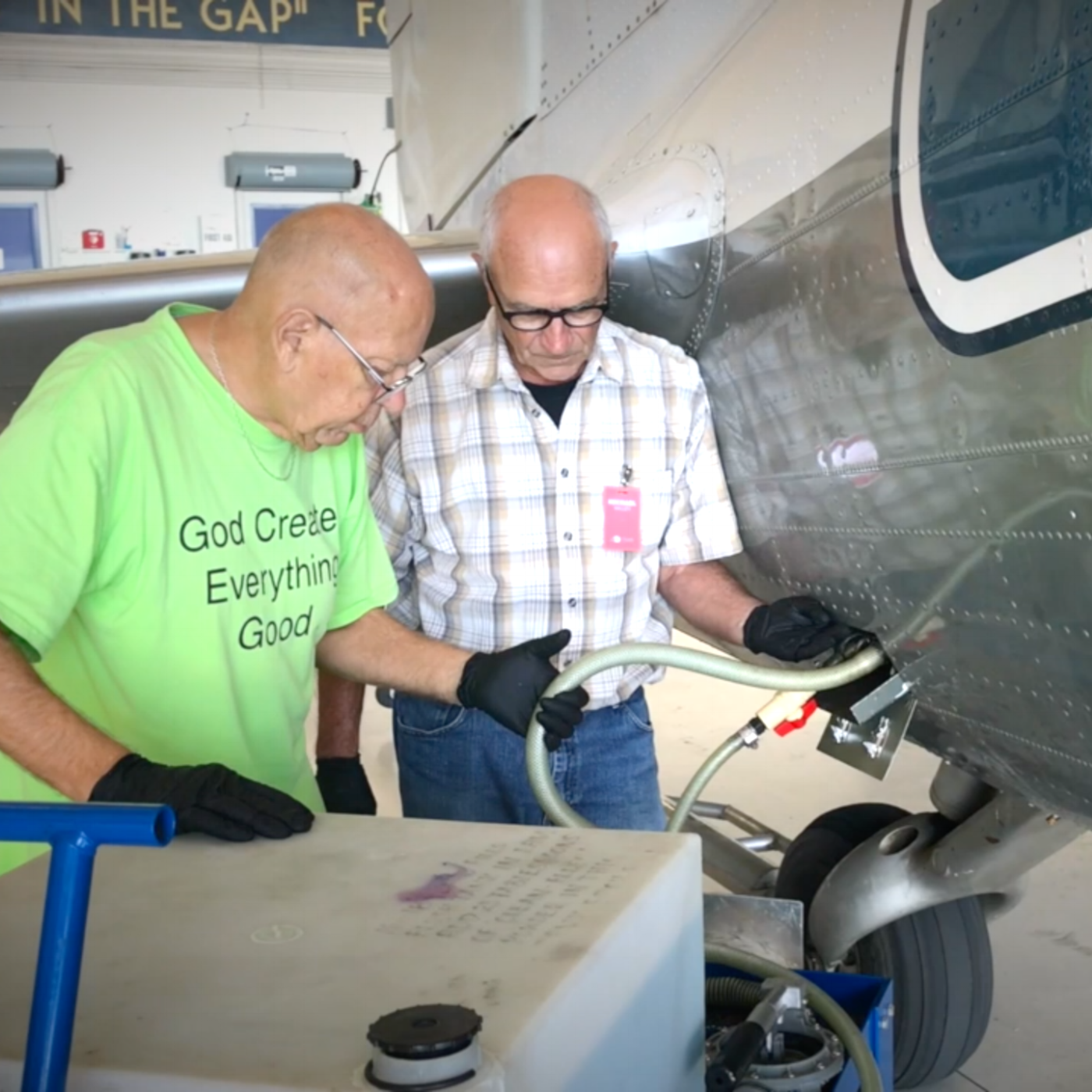 2018 Volunteer of the Year shows how to clean the sewage compartment on the plane.