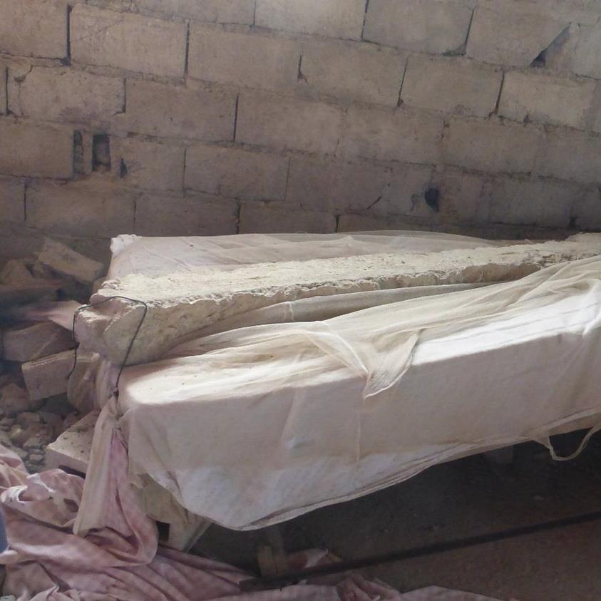 A 300 pound concrete beam lies on a bed after the Port-de-Paix earthquake.