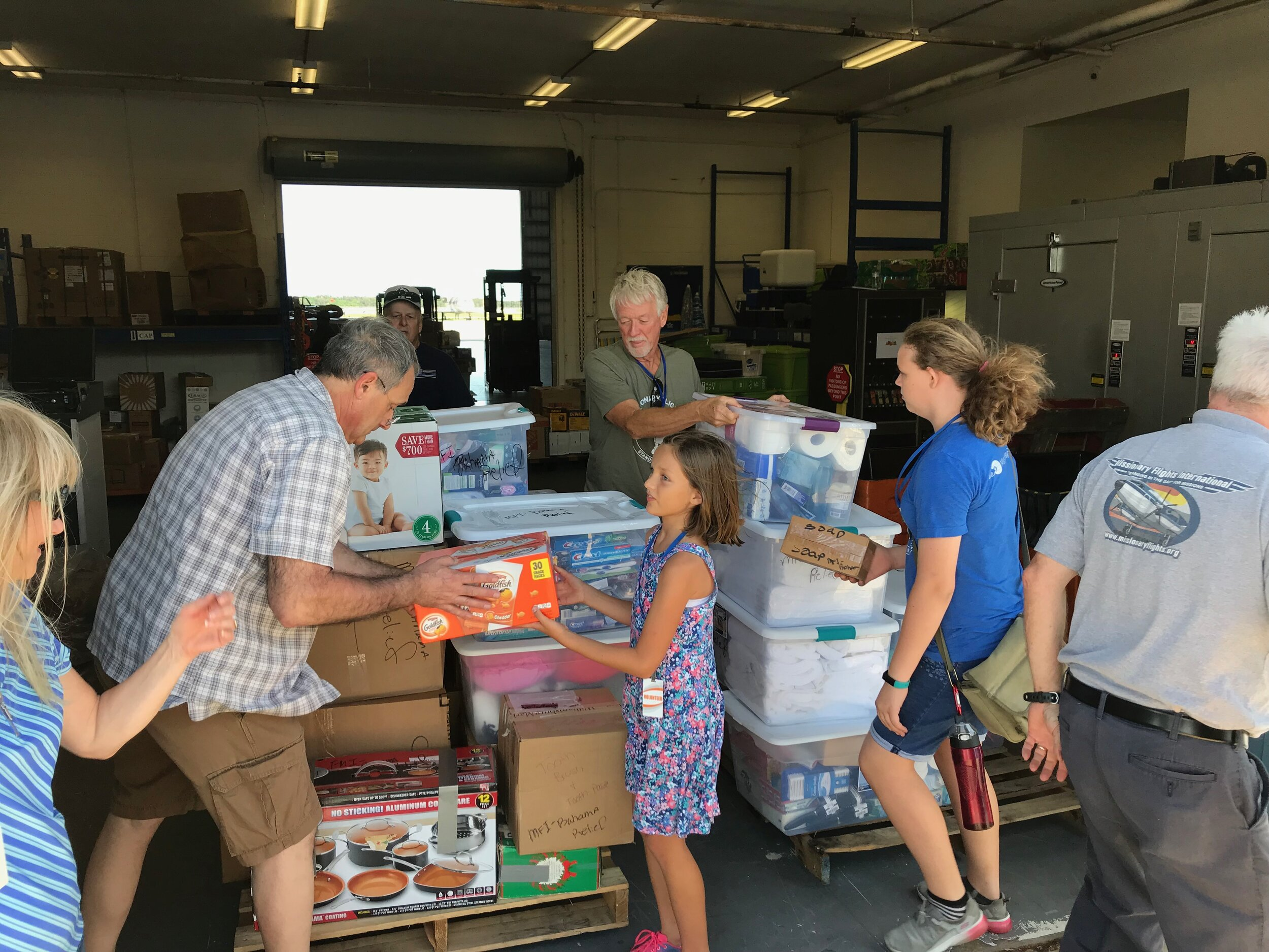 Volunteers help to unload cargo at Missionary Flights International. Among them, are pilot kids Alayna Anders and Tiki Karnes.
