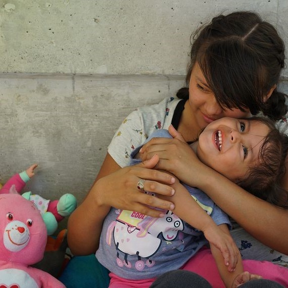 Evelyn Teresa Becerra Ramos, 21, holds her 2-year-old daughter, Jennifer, on the bridge between Matamoros, Mexico, and Brownsville, Texas. She left Guatemala to seek asylum in the U.S. Photo credit: Reynaldo Leal for The Texas Tribune