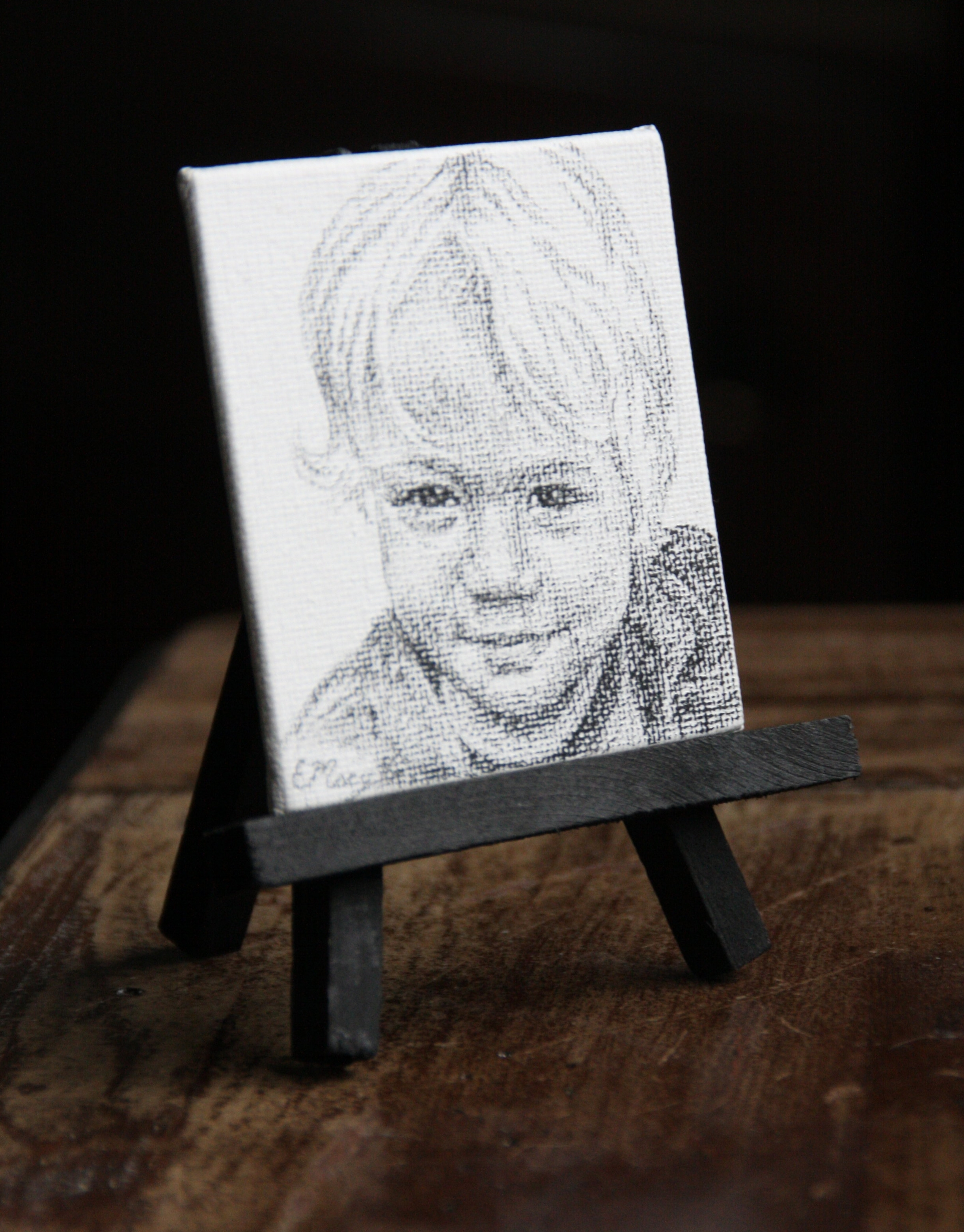 A 3x3 inch charcoal portrait with a black easel perfect for display.