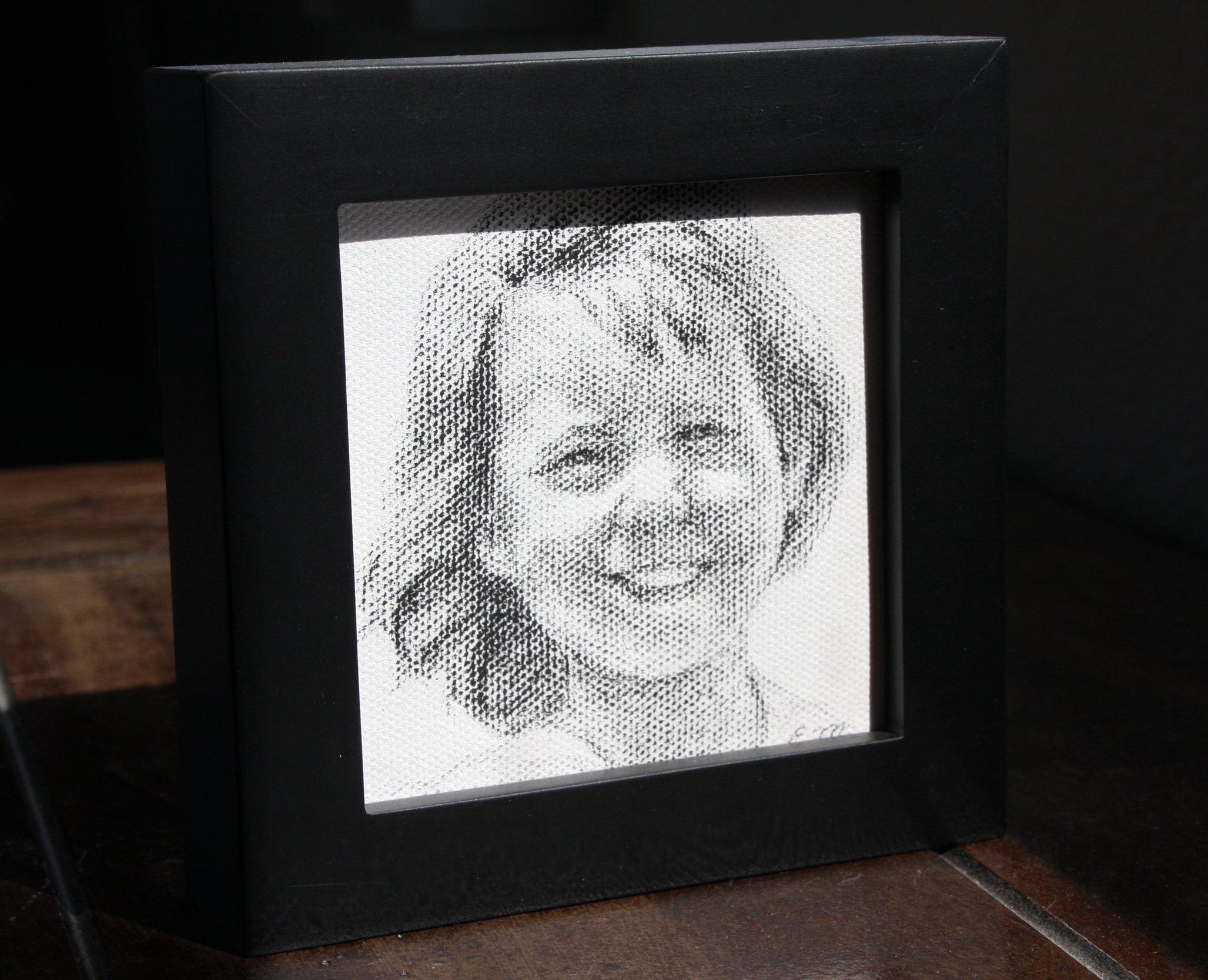 """A framed 4x4"""" charcoal portrait can be hung on the wall, or set on a desk or table top."""