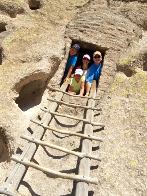 Visitors peek out of one of many cavates, or carved alcoves, at Bandelier. // Photo by Kerry M. Halasz