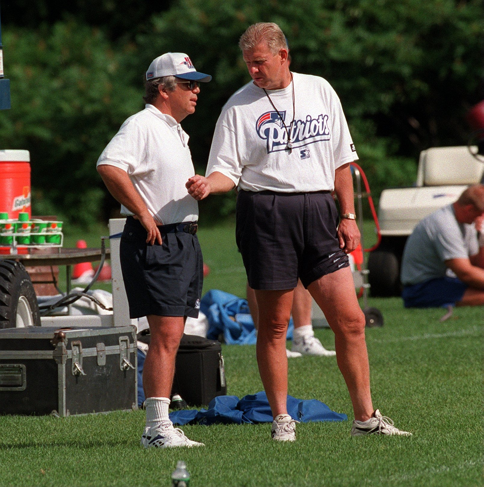 Patriots owner Robert Kraft and head coach Bill Parcells talk during a morning practice on July 22, 1996, in Smith Field, Rhode Island. Kraft had purchased the franchise from James Orthwein in 1994, but Parcells bristled at the new ways of doing things, which diluted the sweeping powers he'd been given under the previous owner. Irreconcilable differences with Kraft would prompt Parcells to leave for the Jets in early 1997 despite having guided New England to Super Bowl XXX. (Tom Landers, Boston Globe, Getty)