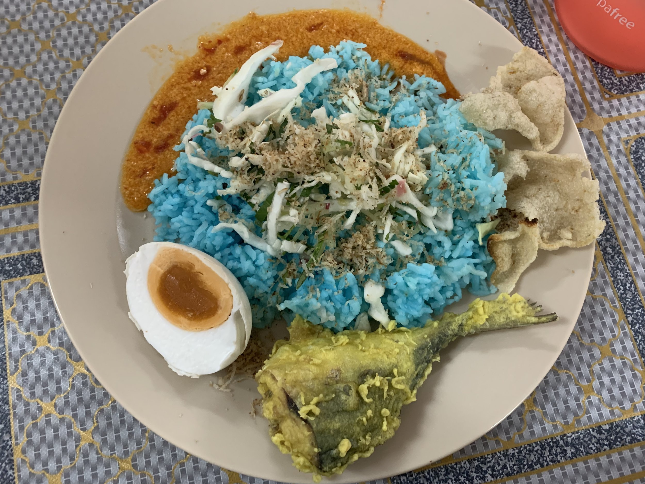 Nasi kerabu: Rice dyed blue with vegetables, salted egg, fish crisps, spicy sauce, fried fish, and fried coconut.