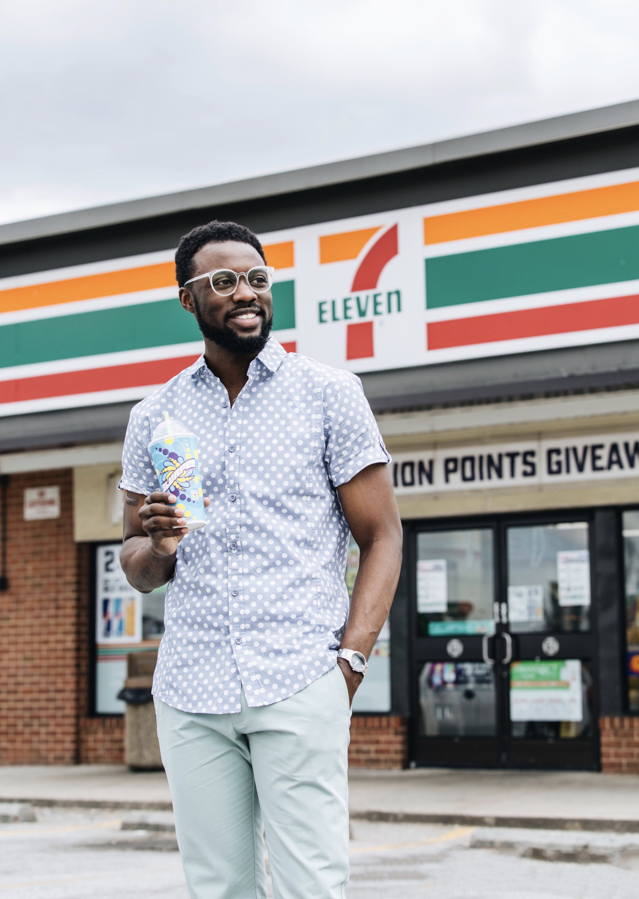 The Creative Gentleman holding a slurpee in front of 7-Eleven. This image was created by The Creative Gentleman for 7-Eleven as part of their 7-Eleven Million Points Giveaway campaign. The campaign encourages people download the 7Rewards App. Overtime the 7Rewrds app is scanned before April 28th, you could win a million points.