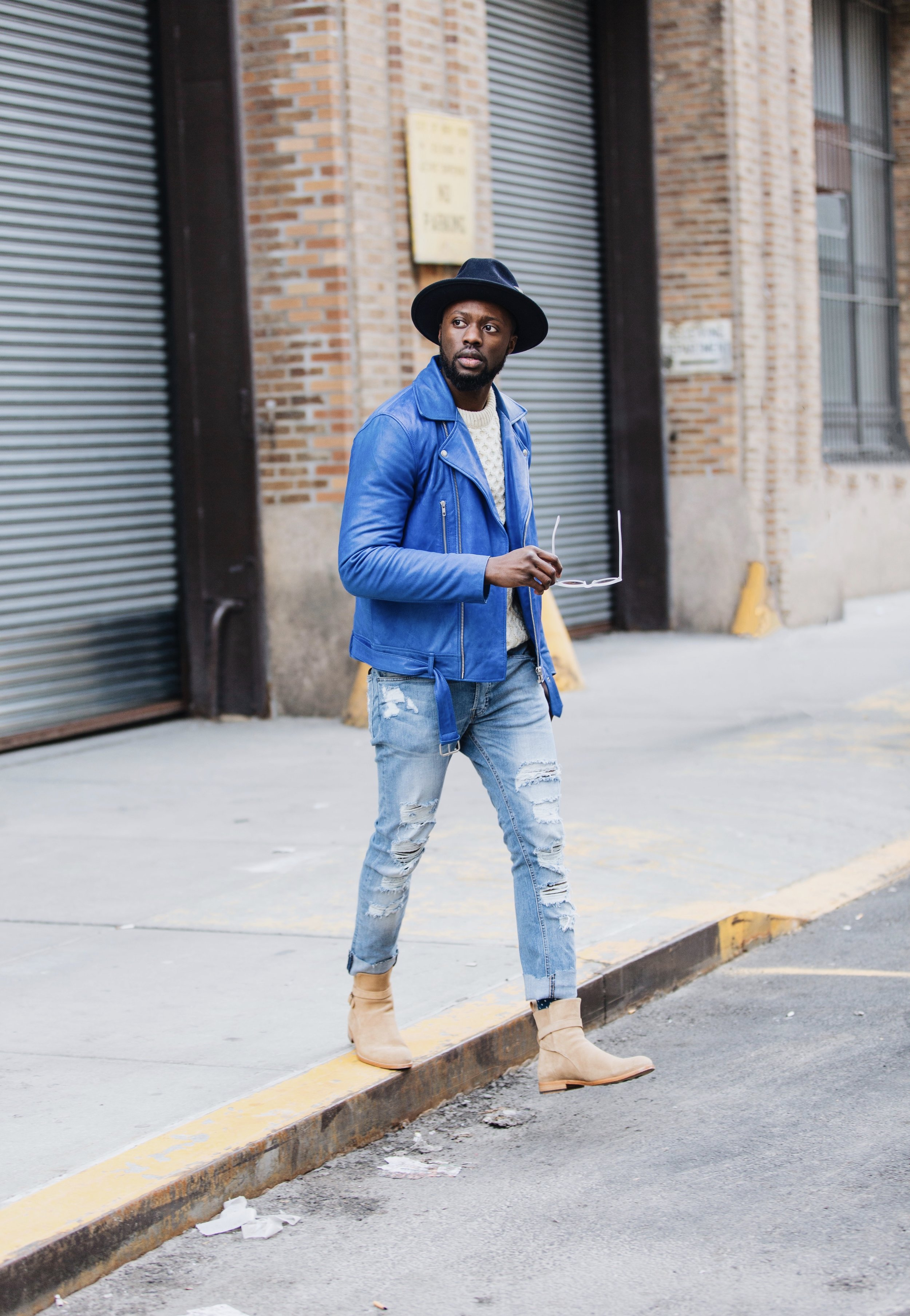 The Creative Gentleman wearing Taft Dylan boot in beige with royal blue leather jacket, cream waffle sweater, light blue ripped jeans, clear framed sunglasses,and navy blue fedora hat. This image was taking as part of The Creative Gentleman and Taft collaboration for New York Fashion Week Men's 2018 NYFWM AW18 on how to style Taft Boots.