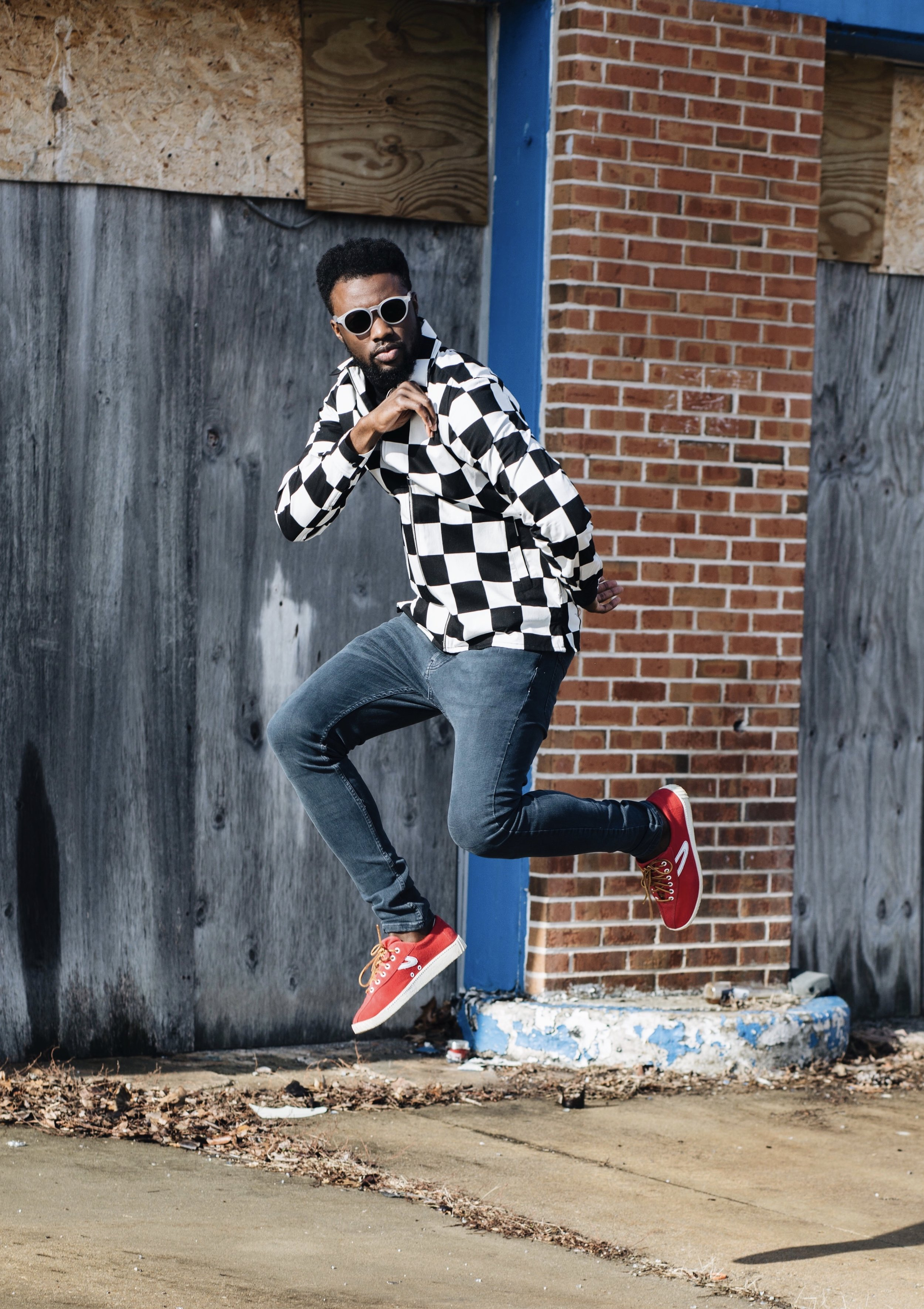 The Creative Gentleman is wearing blue Topman jeans,Topman black and white checkered shirt, red Tretorn Nylite sneakers, and sunglasses. The Creative Gentleman created this image as part of collaboration with Topman for their celebration of being the destination for denim.