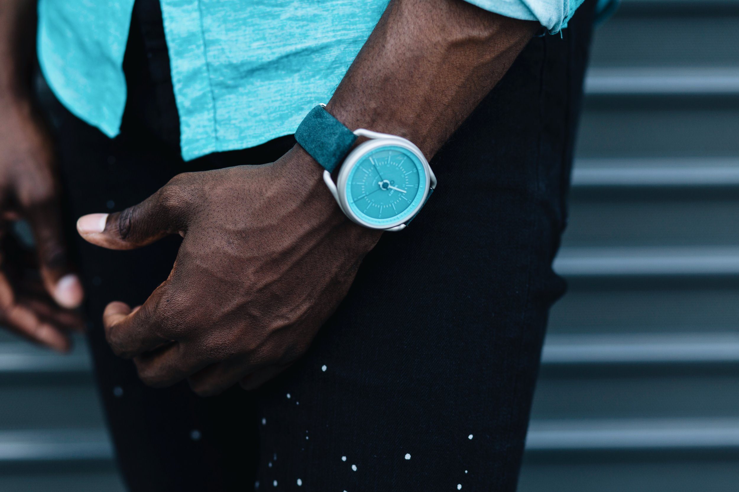 """The Creative Gentleman wearing teal watch by WHAT? Watches, black jeans with white paint spatter, and teal shirt. The image was created as part of The Creative Gentleman and What? Watches """" making time for the unusual"""" campaign."""