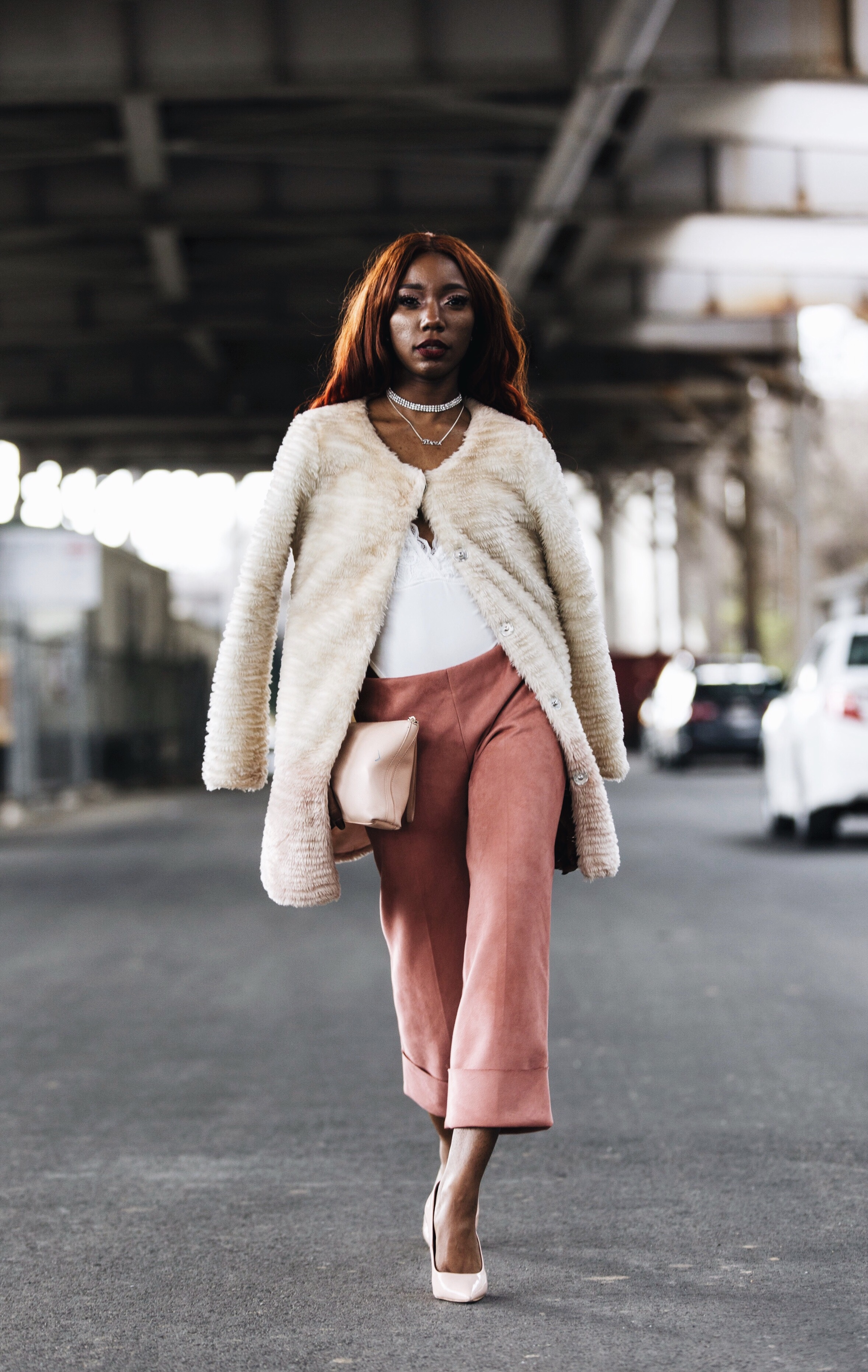 Image of theoriginaljcg model and founder of Marz Enterprise modeling agency wearing pink suede trousers, white top, fur jacket, and light pink heels captured by photographer The Creative Gentleman for Fashion Bomb Daily. This image was taken during the Conversations with Claire brunch event in Washington, D.C.