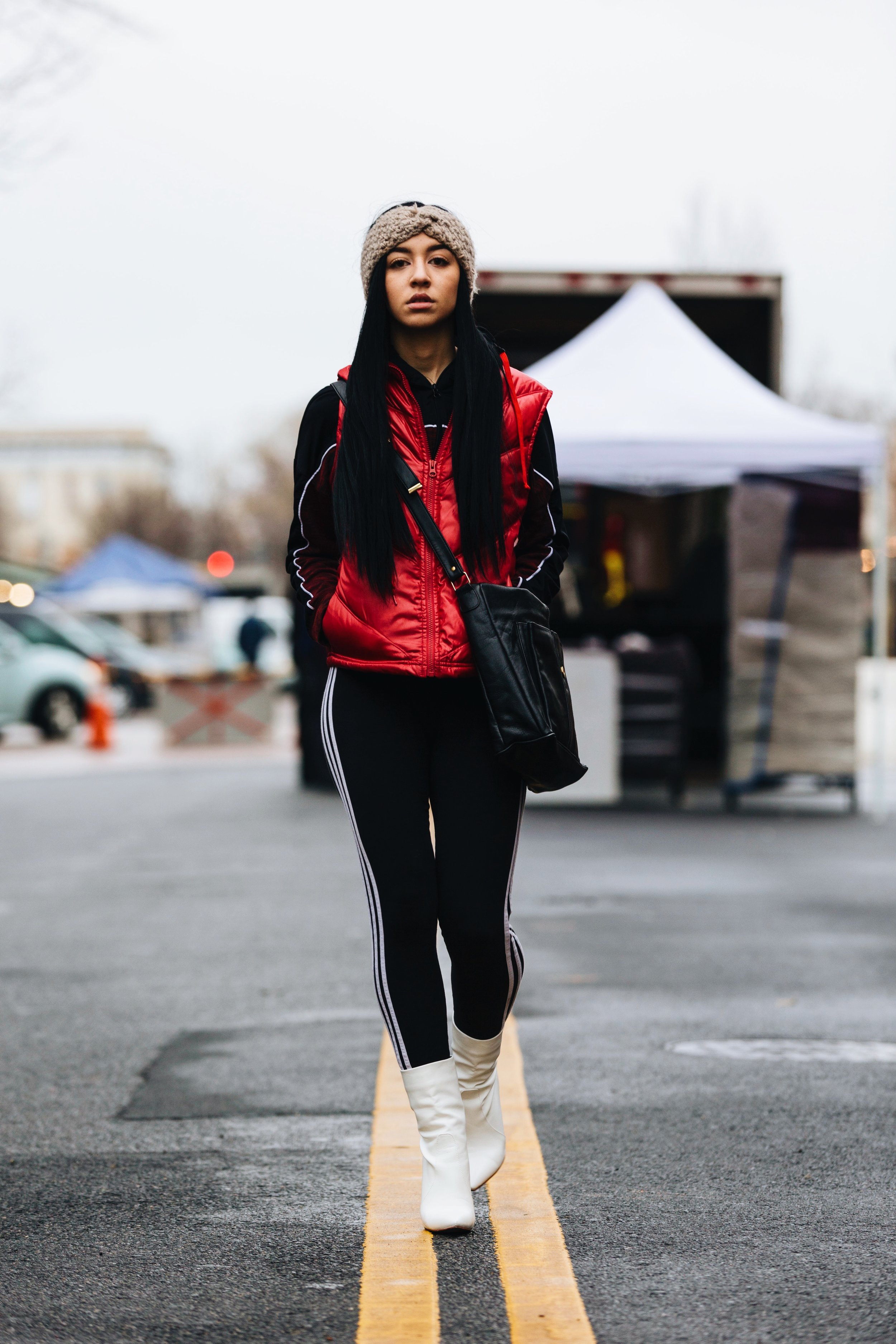 Photograph of DMV model Jazmyne Paris wearing a knitted headband, red puffer vest, black track jacket, Adidas leggings, black tote bag, and white boots captured by photographer The Creative Gentleman during Street Meet Dc Eastern Market DC meet up.