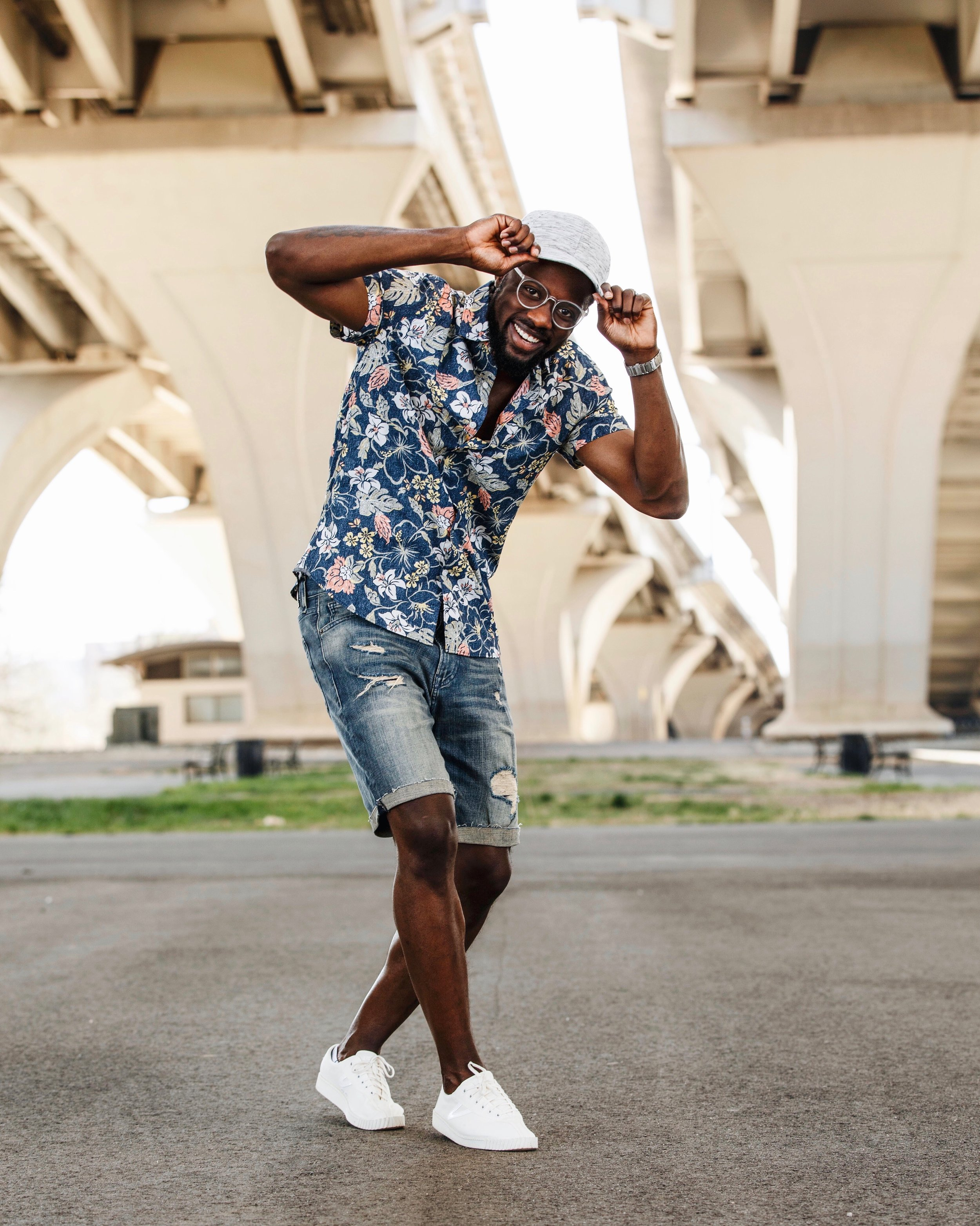 """Menswear influencer The Creative Gentleman wearing ball cap, blue floral short sleeve shirt, slim fit denim shorts with rips, clear framed glasses, and cream Tretorn sneakers. This picture was taken for Express Mens """"Express the Moment"""" Campaign."""