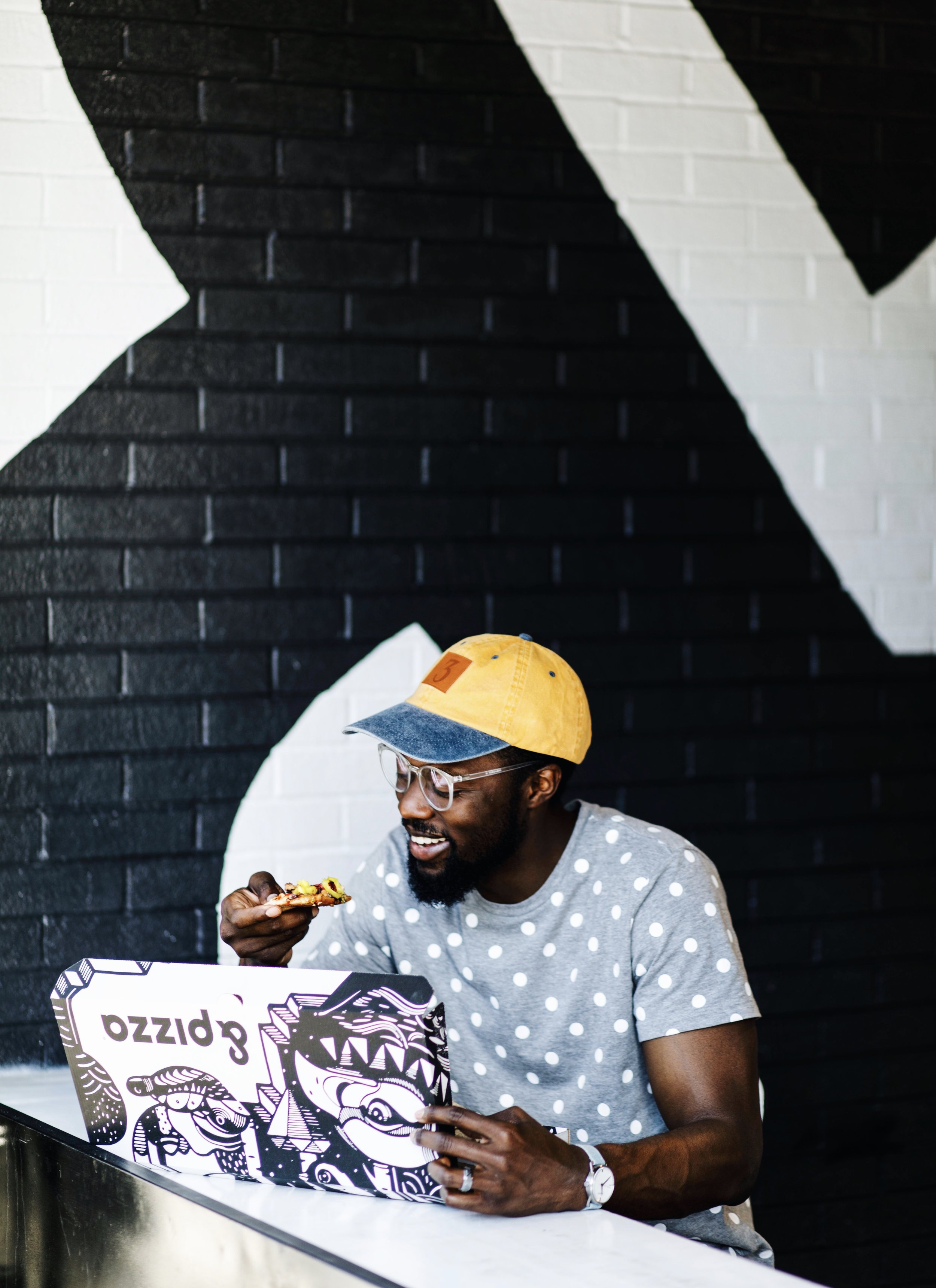 Image of brand influencer the creative gentleman holding a slice of &pizza with a black and white &pizza box. He is wearing a grey tee shirt with white polka dots, clear framed glasses, a yellow hat with a number three in the front, and a watch with a denim strap.
