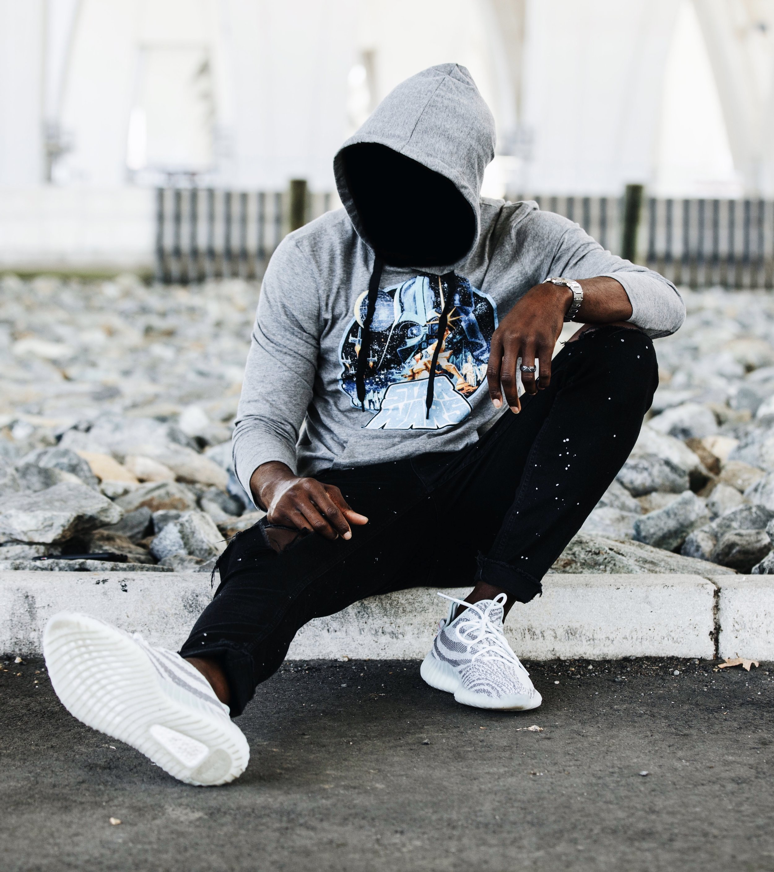 Brand influencer the creative gentleman wearing a grey hoody with Star Wars written on it, black ripped denim with white paint spatter, and Yezzy 350 Blue Tint sneakers.