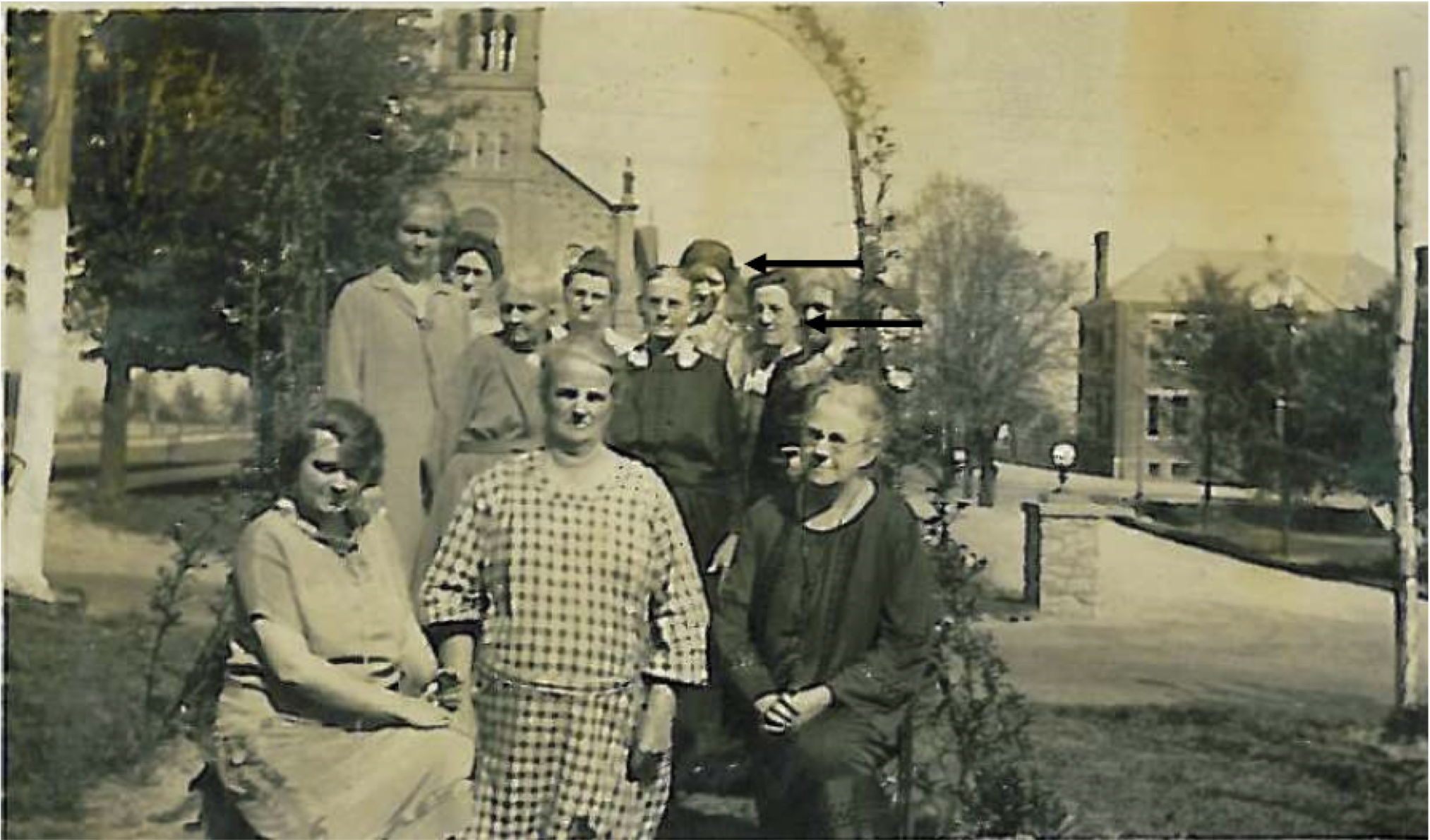 Katie Reimerink Klawitter in plaid dress in front of Our Lady Victory Church, Neeb Road in Delhi. Also pictured in the rear by the top arrow is Anna Sandmann, a daughter-in-law of Katie Reimerink and Eduard Klawitter. Also Rosa Klawitter Hubert their daughter, lower arrow.