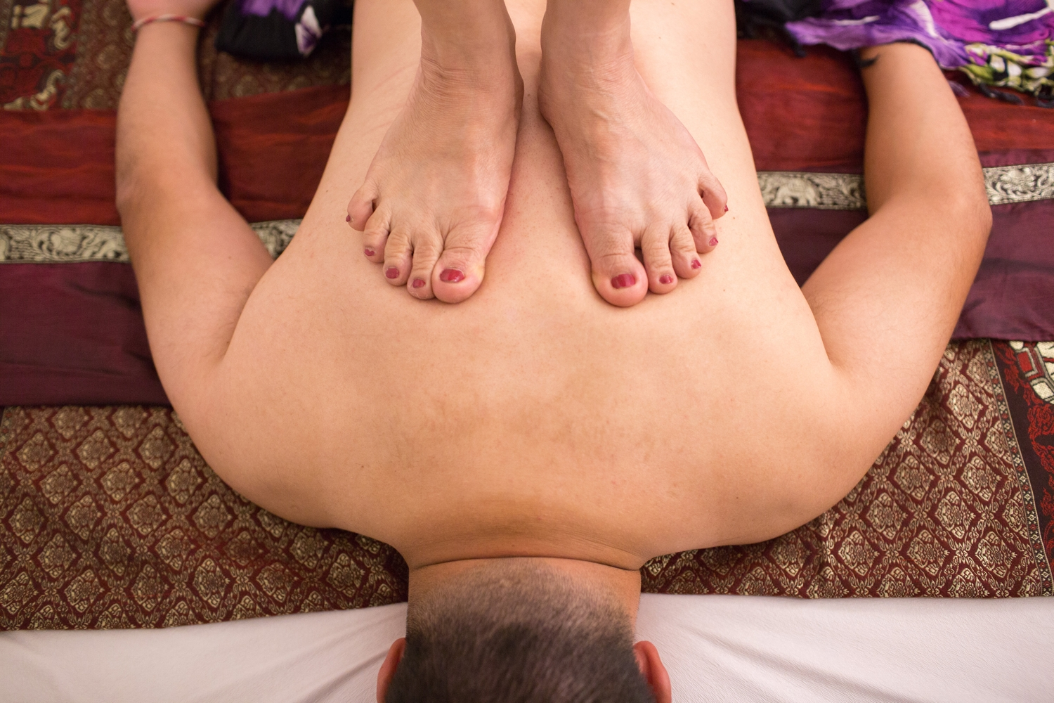 thai massage with woman standing on mans back
