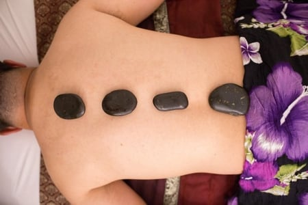 hot stones on mans back for a thai massage