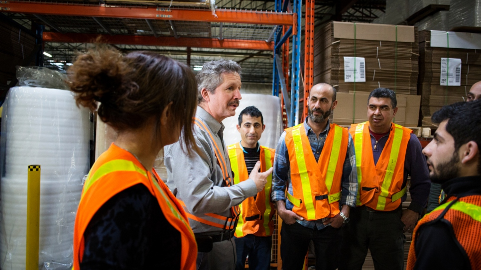 Estill speaking to employees at his company warehouse (Annie Sakkab / UNHCR)