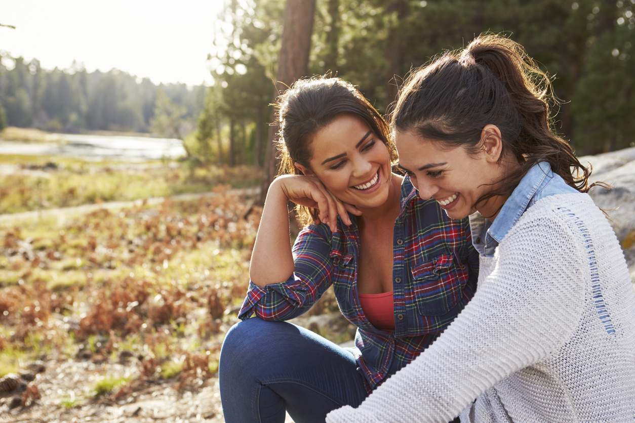 two girls laughing in a field