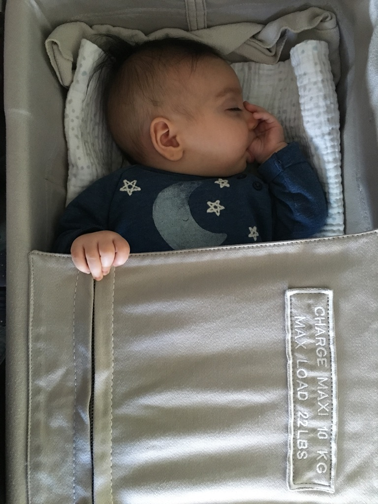 One of the very few times she ever slept in the bassinet on the plane.