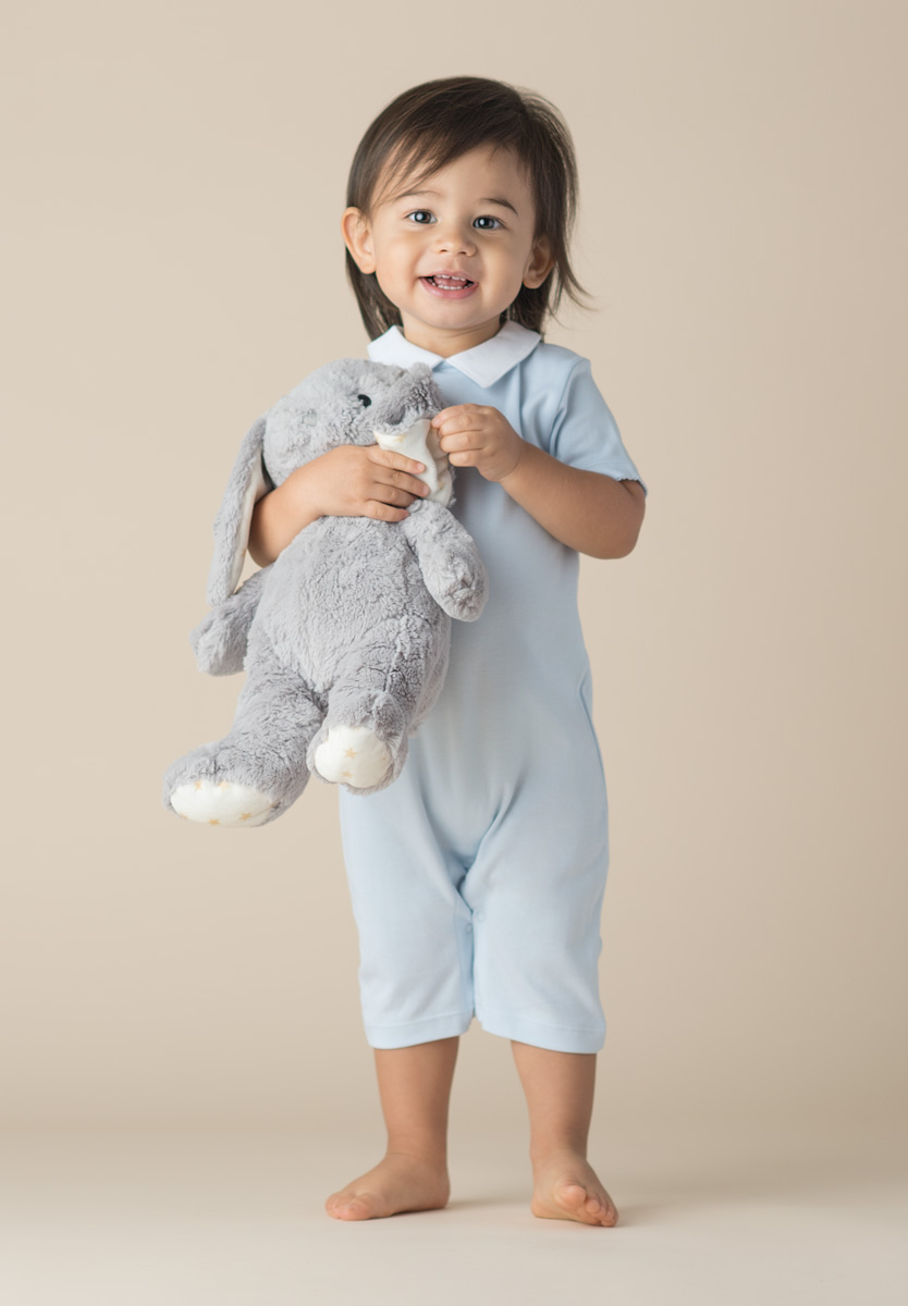 studio portrait of a child with a stuffed animal
