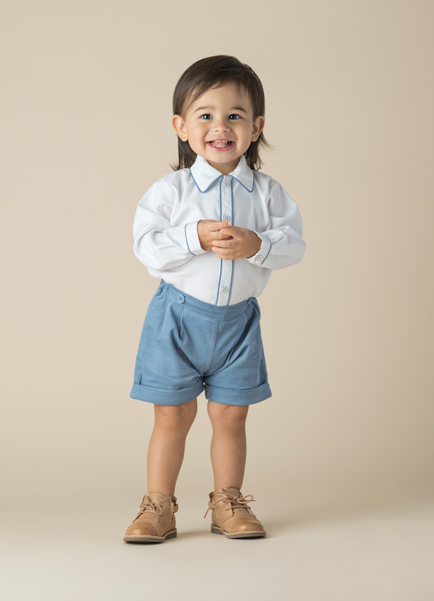 Studio portrait of toddler wearing a white shirt with blue shorts by Rachel Riley