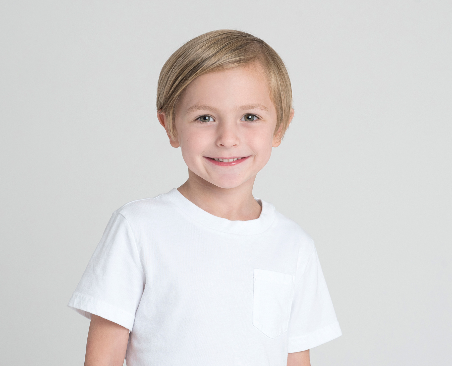 studio portrait of a boy wearing a white shirt