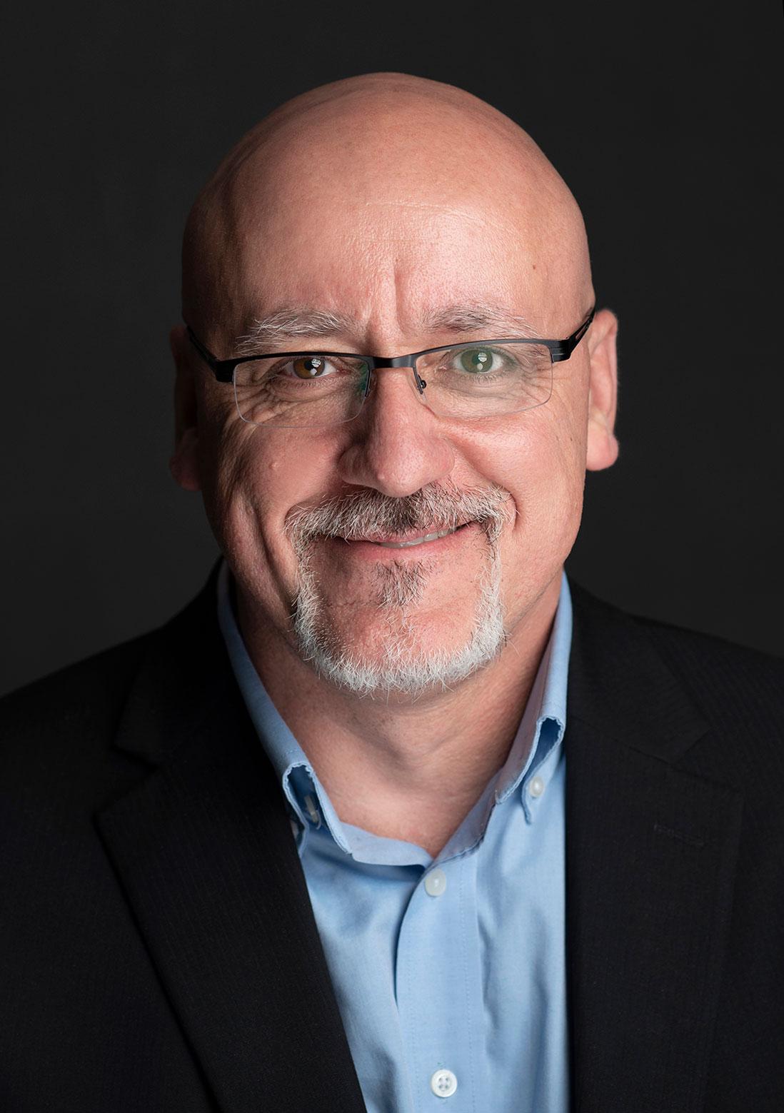 Studio headhshot of man wearing glasses