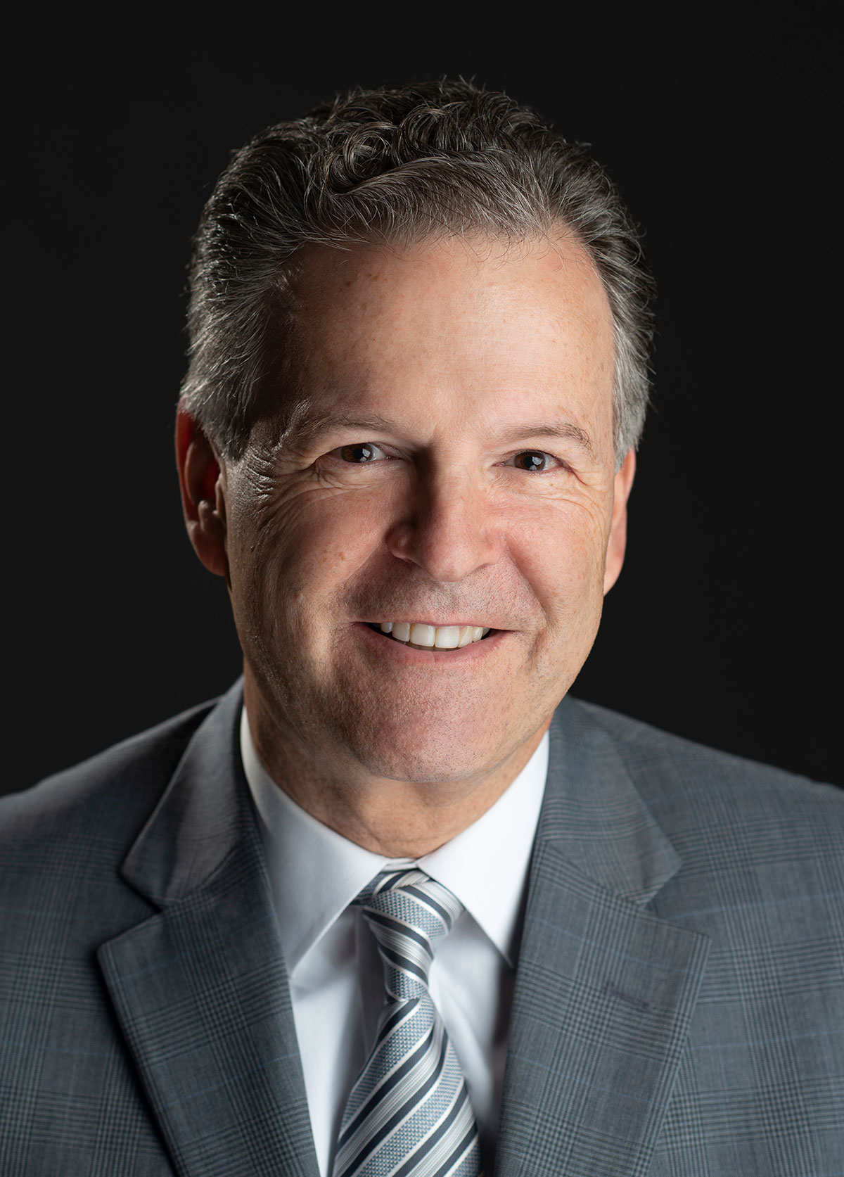 Corporate headshot of man wearing gray suite