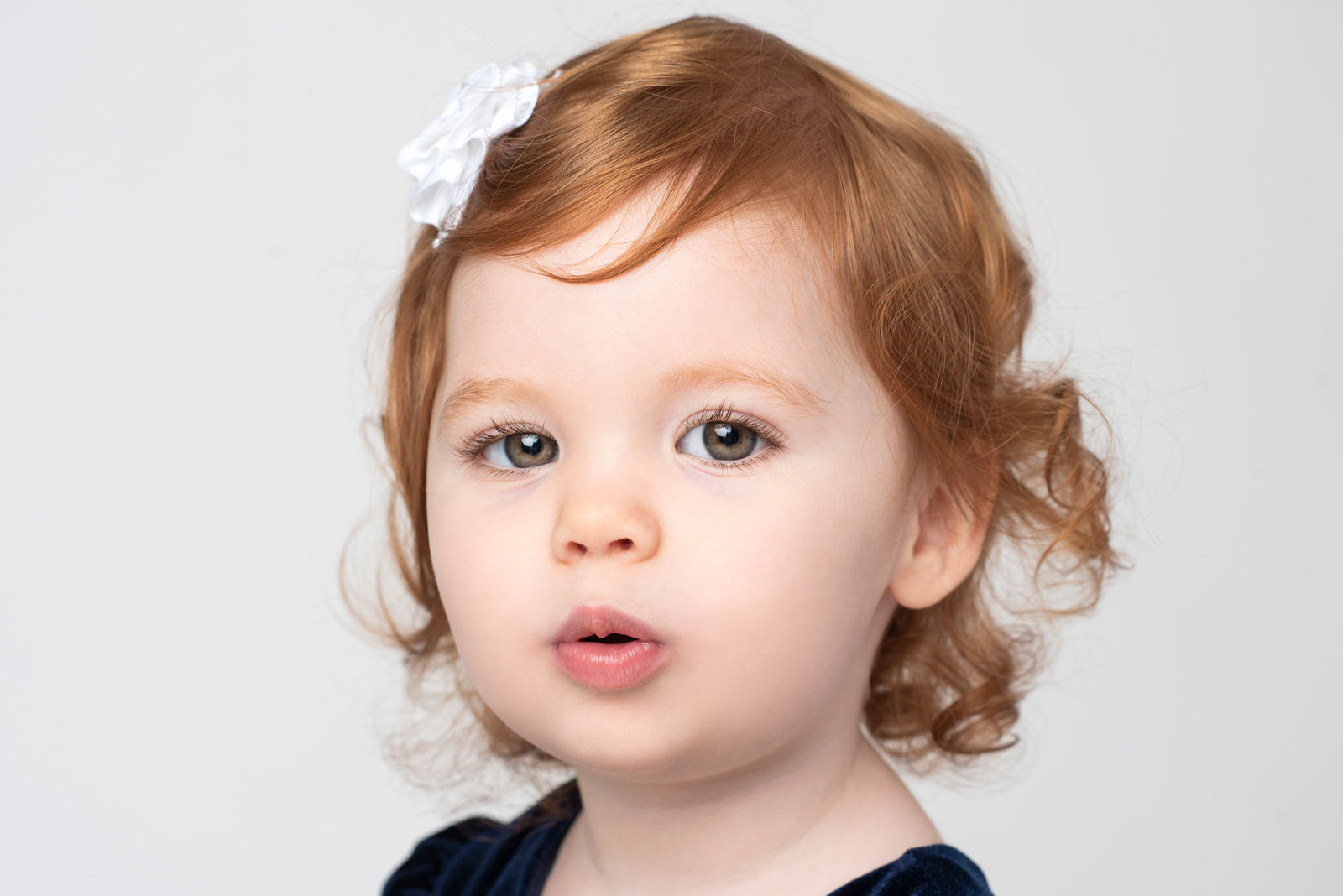 Christmas photo of redheaded toddler girl with white bow
