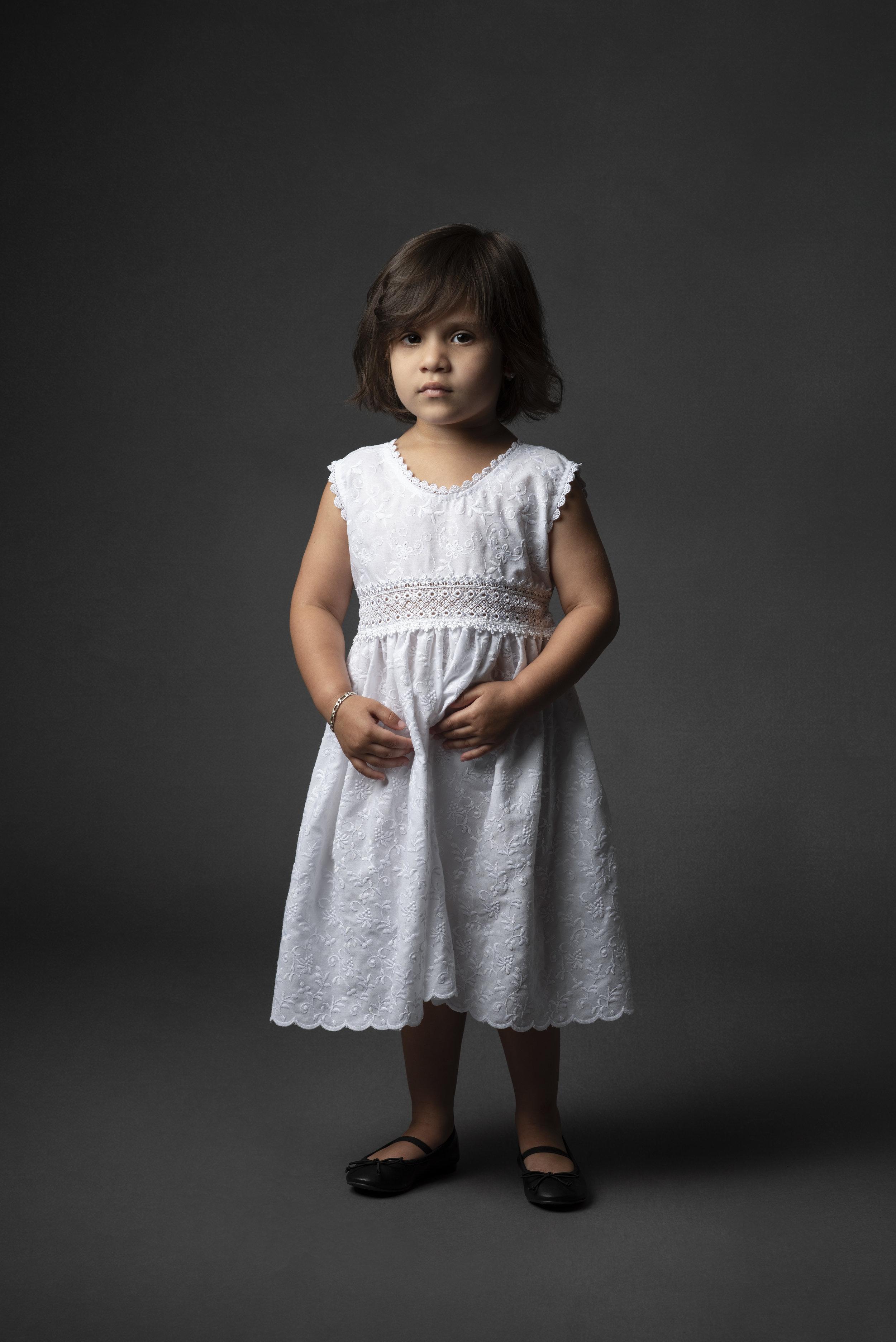 Studio portrait of little girl in white dress on gray background.
