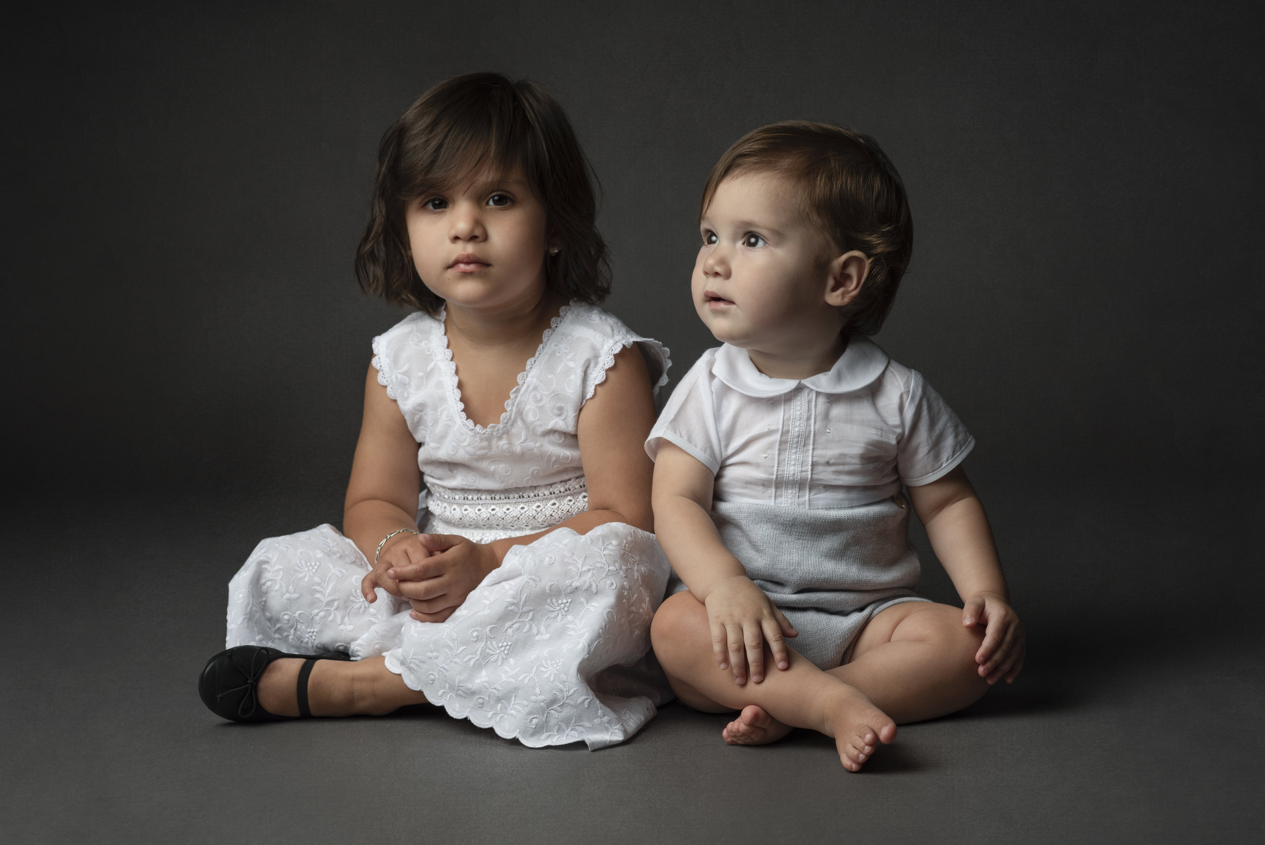 Studio portrait of siblings wearing white and gray